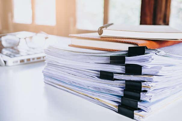 Online Mahnverfahren: Papierstapel und Laptop